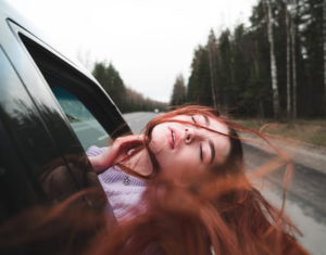 girl hanging out car window